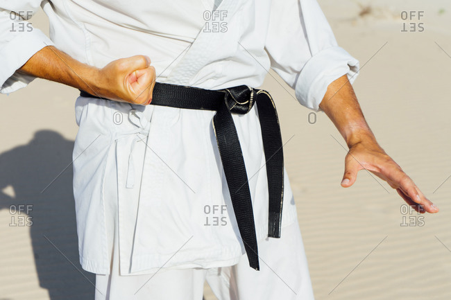 Close-up of mature man practicing karate while standing at beach