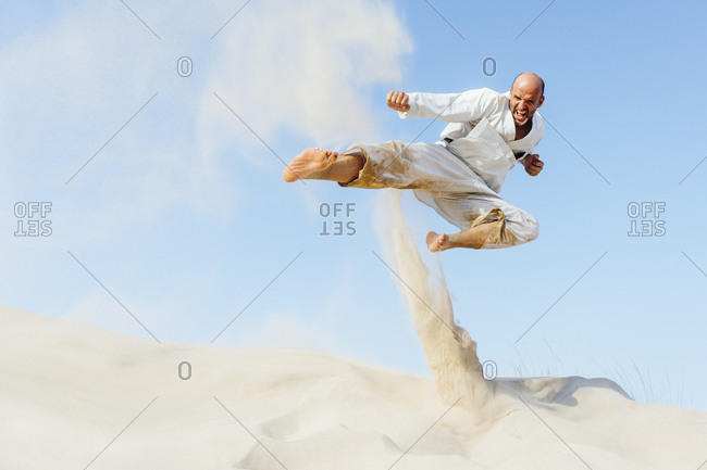 Mature man jumping while practicing karate on sand at beach against sky