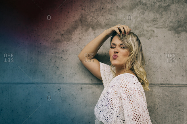 Young woman making pout while leaning on wall