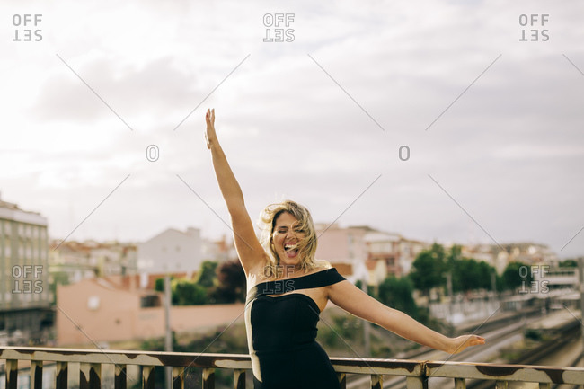 Excited young woman standing with arms outstretched in city