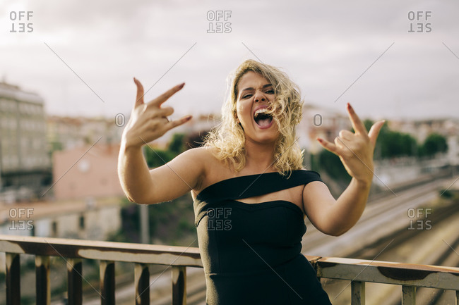 Excited woman wearing black dress showing rock and roll sign in city