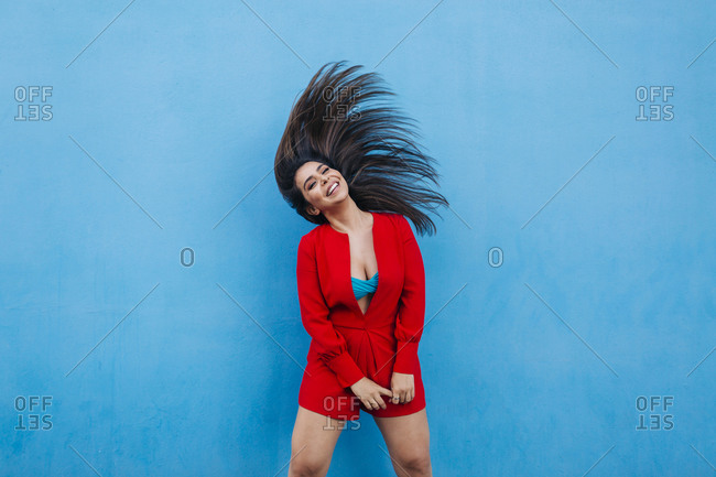 Laughing young woman shaking her head in front of blue wall