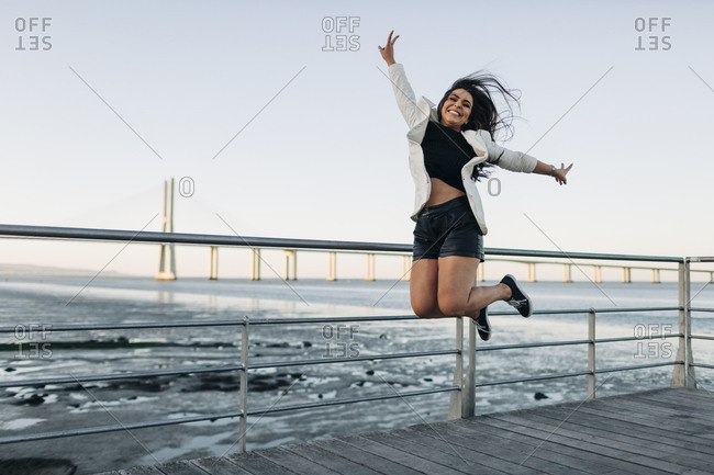 Young woman jumping on waterfront