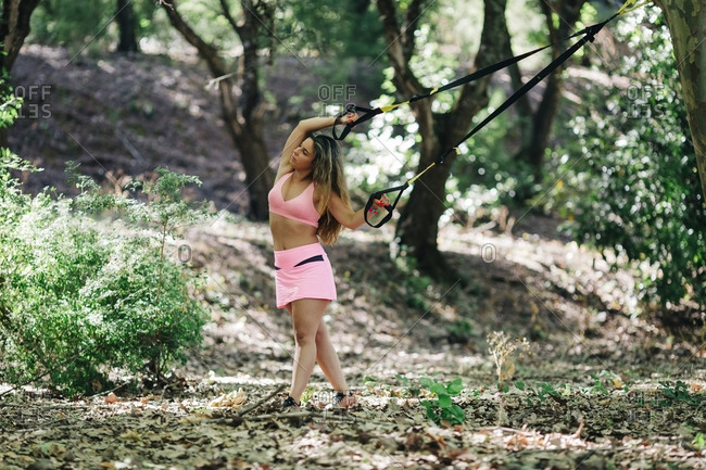 Young woman with arms raised pulling straps while standing in park
