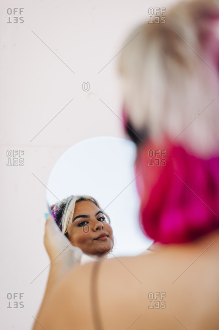 Woman looking her reflection in hand mirror