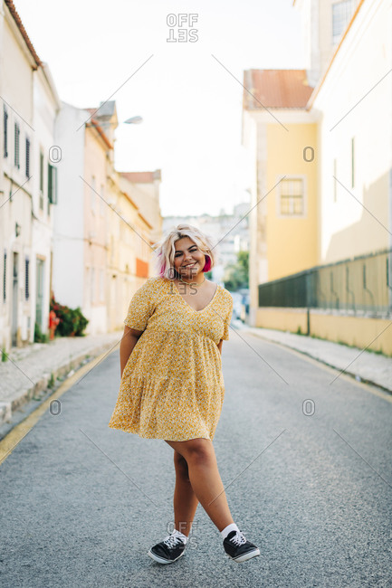 Smiling plus size woman standing with crossed leg on road