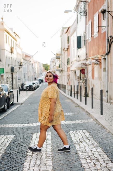 Young body positive woman crossing street in city