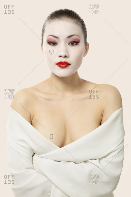 Young woman with opera make-up wrapped in blanket against white background
