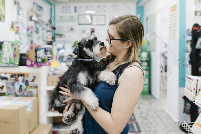 Happy woman carrying schnauzer while standing in pet salon