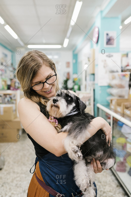 Happy female groomer embracing schnauzer while standing in pet salon