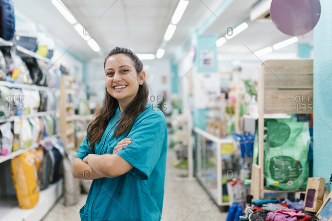 Smiling female groomer with arms crossed standing in pet shop