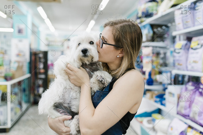 Close-up of female groomer kissing west highland white terrier in pet salon