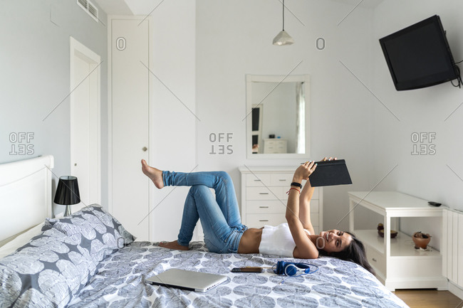 Smiling mid adult woman holding book while resting on bed at home