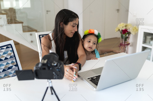 Mother looking at daughter standing beside her while filming video on table