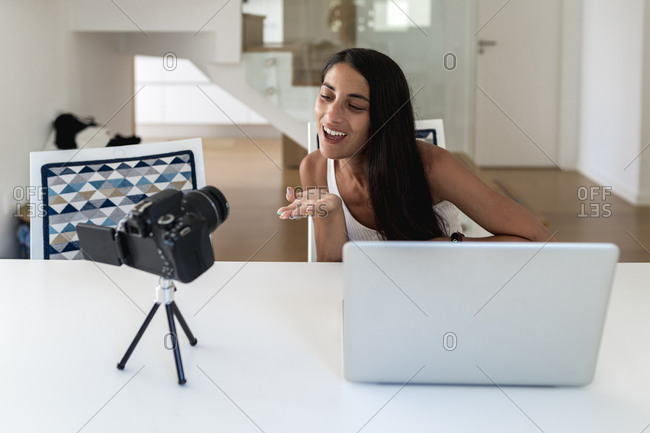Cheerful woman filming video with camera on table at home
