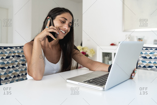 Smiling mid adult woman talking over mobile phone while using laptop on table at home
