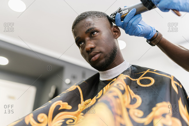 Male barber wearing glove with razor cutting young man's hair in salon