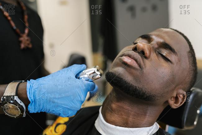 Close-up of barber wearing glove cutting young man's beard in salon