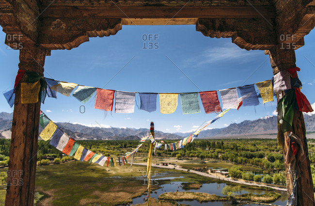 India- Ladakh- Colorful prayer flags hanging between two old columns