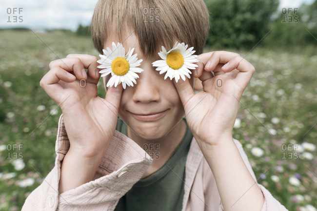 Close-up of boy hiding eyes with chamomile flowers