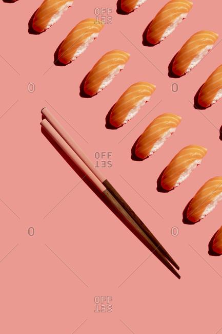 Studio shot of chopsticks and salmon nigirizushi pieces