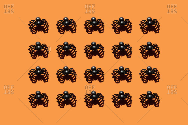 Pattern of black plastic spiders against orange background