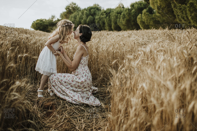 Mother and daughter spending leisure time in wheat field