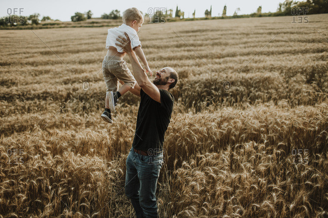 Father spending leisure time with son in wheat farm