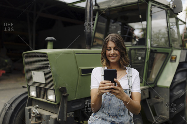 Young woman using mobile phone at a tractor on a farm