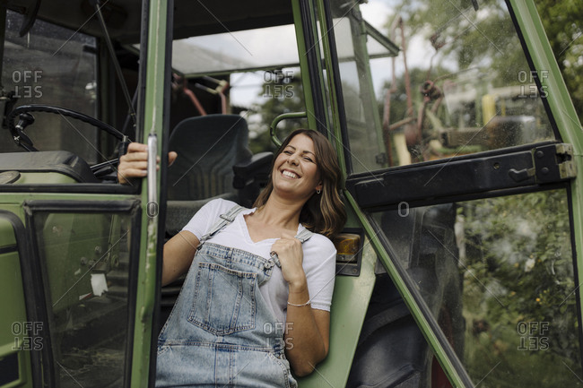 Cheerful young woman at a tractor in the countryside