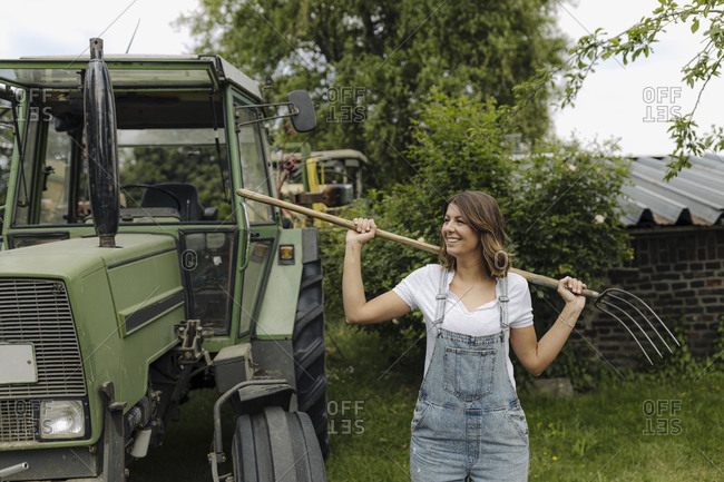 Smiling young woman with hay fork standing at a tractor in the countryside