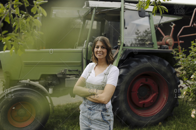 Portrait of a confident young woman standing at a tractor on a farm
