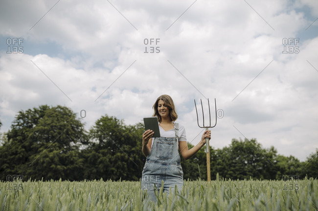 Young woman with hay fork and tablet standing in a grain field in the countryside