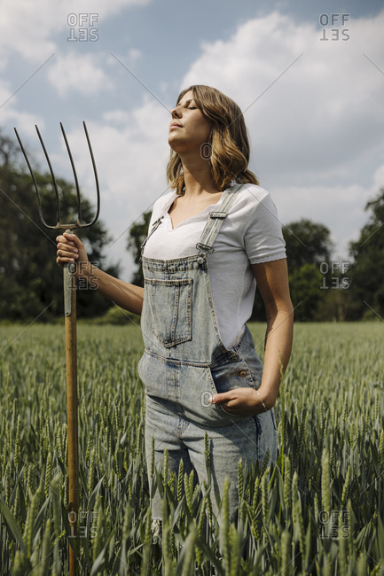 Young woman with hay fork standing in a grain field in the countryside