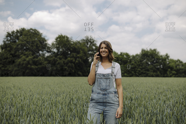 Young woman on the phone in a grain field in the countryside