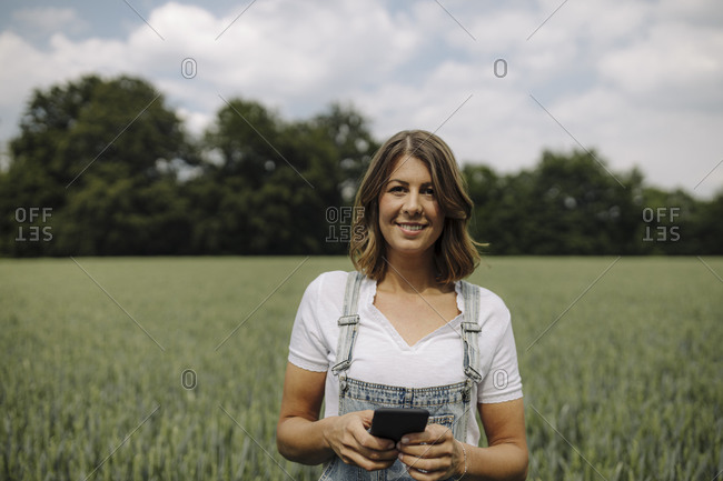 Young woman holding smartphone in a grain field in the countryside