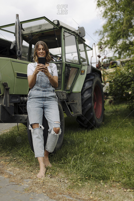 Young woman using mobile phone at a tractor in the countryside