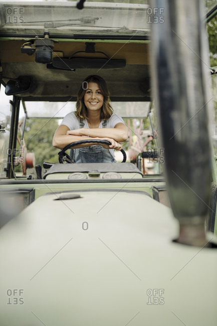 Portrait of confident young woman in a tractor