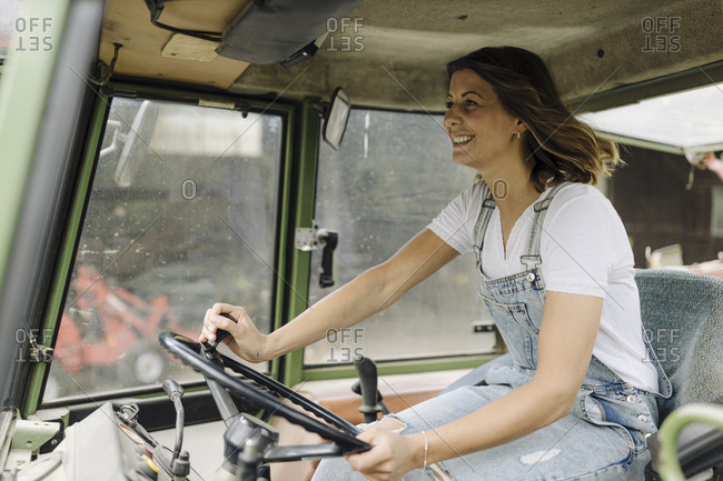 Happy young woman driving tractor