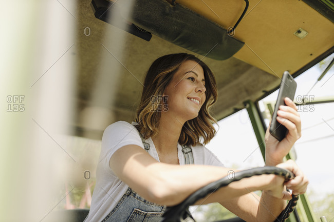 Smiling young woman using mobile phone in a tractor