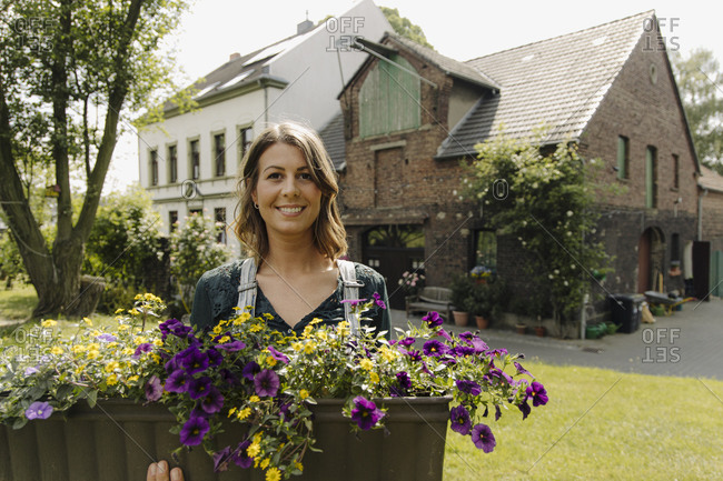 Portrait of smiling young woman with flower box at a farmhouse