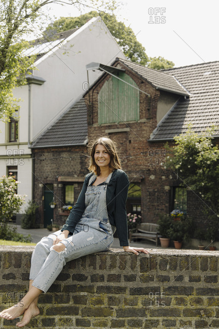 Portrait of smiling young woman sitting on a brick wall at a farmhouse