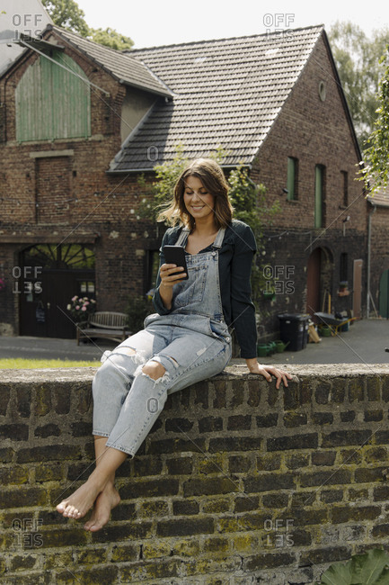 Young woman sitting on a brick wall at a farmhouse using smartphone