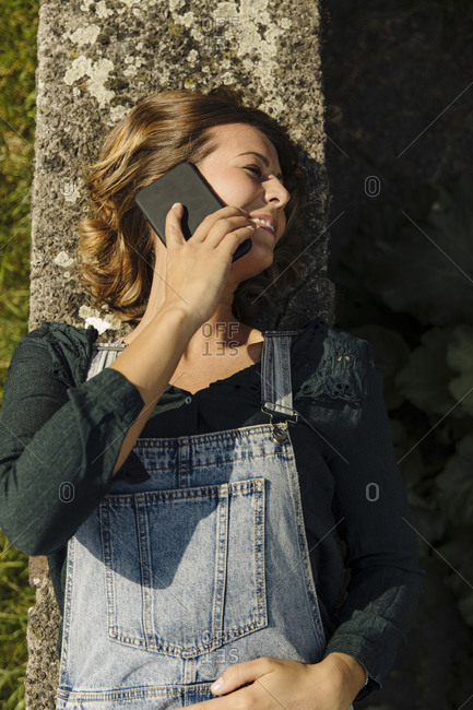 Young woman lying on a wall talking on the phone