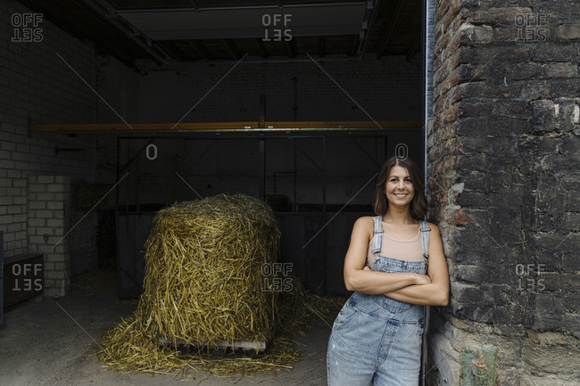 Portrait of smiling young woman leaning against brick wall at a barn on a farm