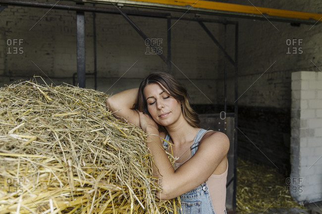 Young woman with closed eyes leaning on straw in a barn on a farm