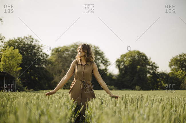 Young woman in a grain field in the countryside touching ears