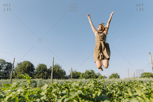 Happy young woman jumping in a vegetable patch