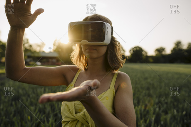 Young woman wearing VR goggles in a grain field in the countryside