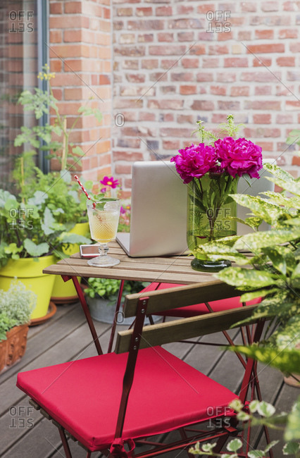 Small working space on balcony surrounded with summer plants